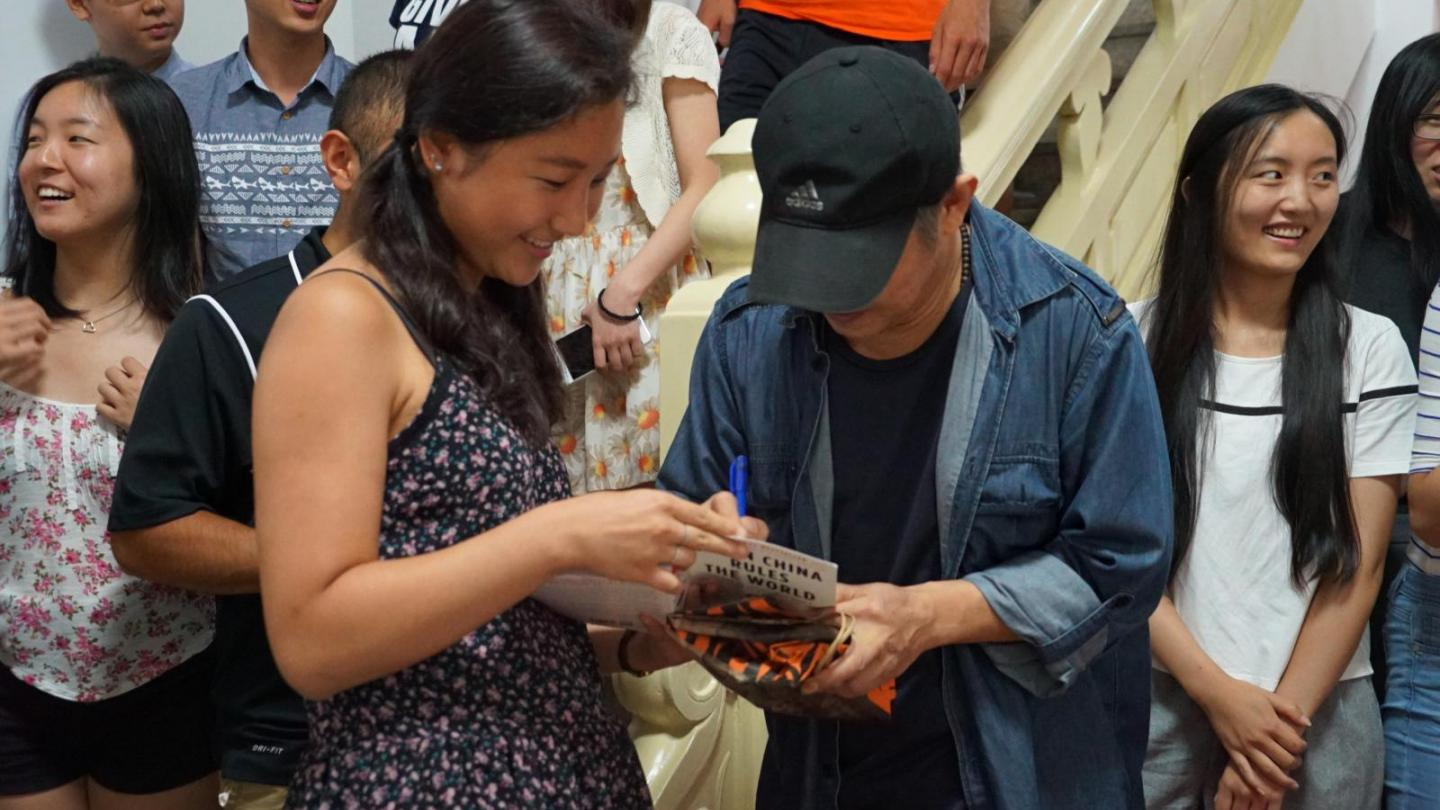 Cadee Qiu '18 having her book autographed by Jet Li.  Teresa Tang '18 in the background.